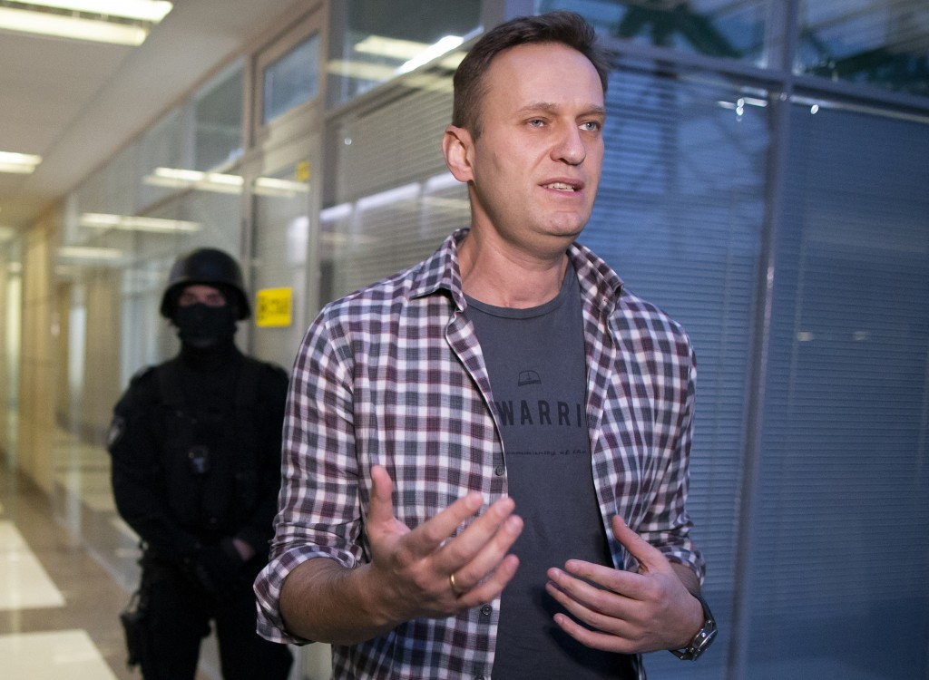FILE - In this file photo taken on Thursday, Dec. 26, 2019, Russian opposition leader Alexei Navalny speaks to the media as policemen stand guard at t...