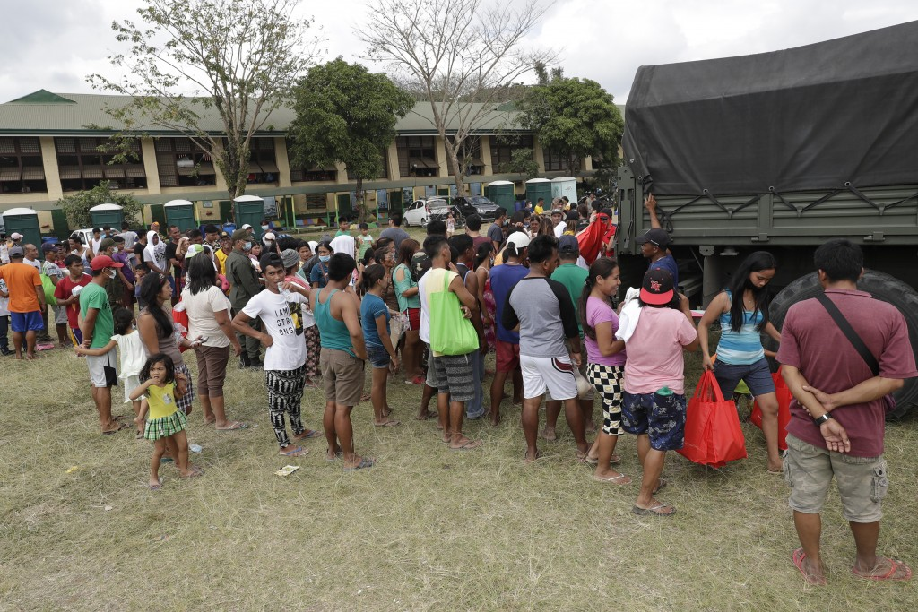 Evacuees gather to receive relief goods at an evacuation center in Alfonso, Cavite province, southern Philippines on Saturday Jan. 18, 2020. The Taal ...
