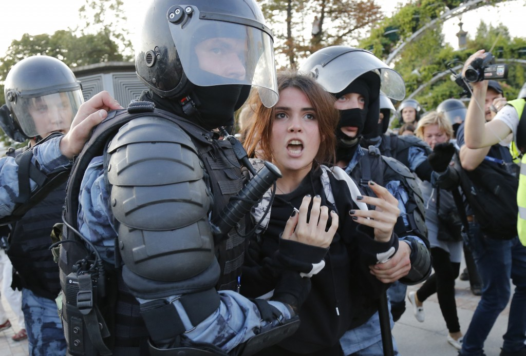 FILE - In this file photo taken on July 27, 2019, police officers detain a woman during an unsanctioned rally in the centre of Moscow, Russia. Instead...