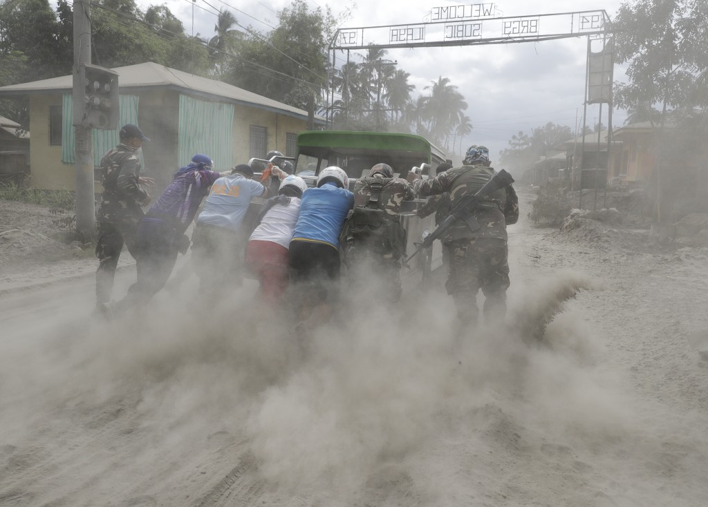Police and military help push a vehicle along a road covered in volcanic ash at a village beside Taal volcano where residents have evacuated to safer ...