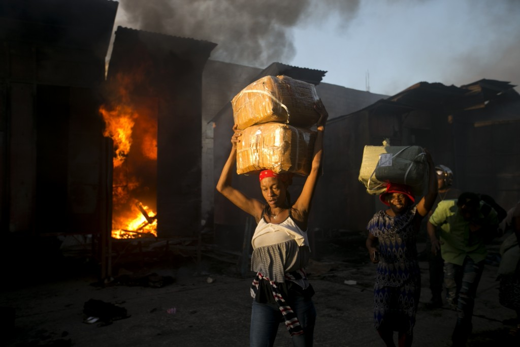 Vendors carry salvaged merchandise from the burned ruins of the Guerite Market that was engulfed in flames in Port-au-Prince, Haiti, early Tuesday, Ja...