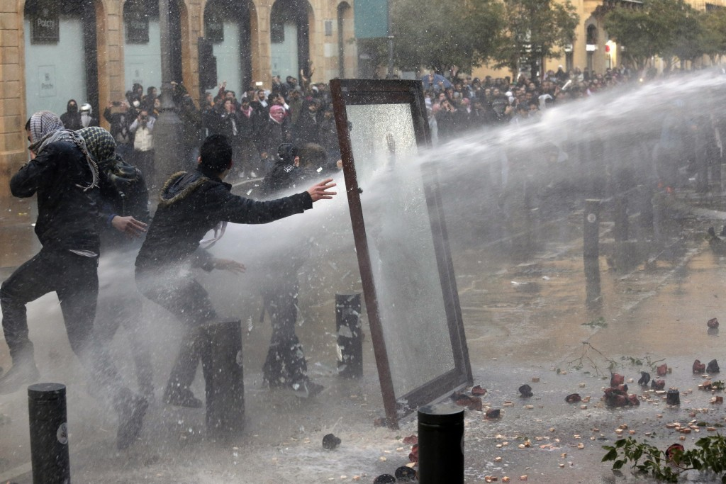 Riot police use a water cannon against anti-government demonstrators at a road leading to the parliament building in Beirut, Lebanon, Saturday, Jan. 1...