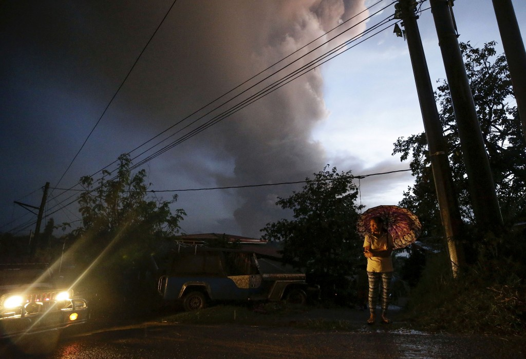 A resident prepares to evacuate as smoke rises from the erupting Taal Volcano, Sunday Jan. 12, 2020, in Tagaytay, Cavite province, outside Manila, Phi...