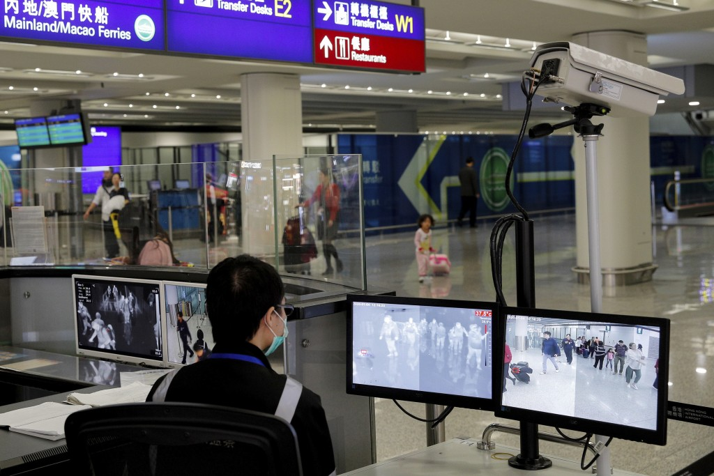 FILE - In this Jan. 4, 2020, file photo, a health surveillance officer monitors passengers arriving at the Hong Kong International airport in Hong Kon...