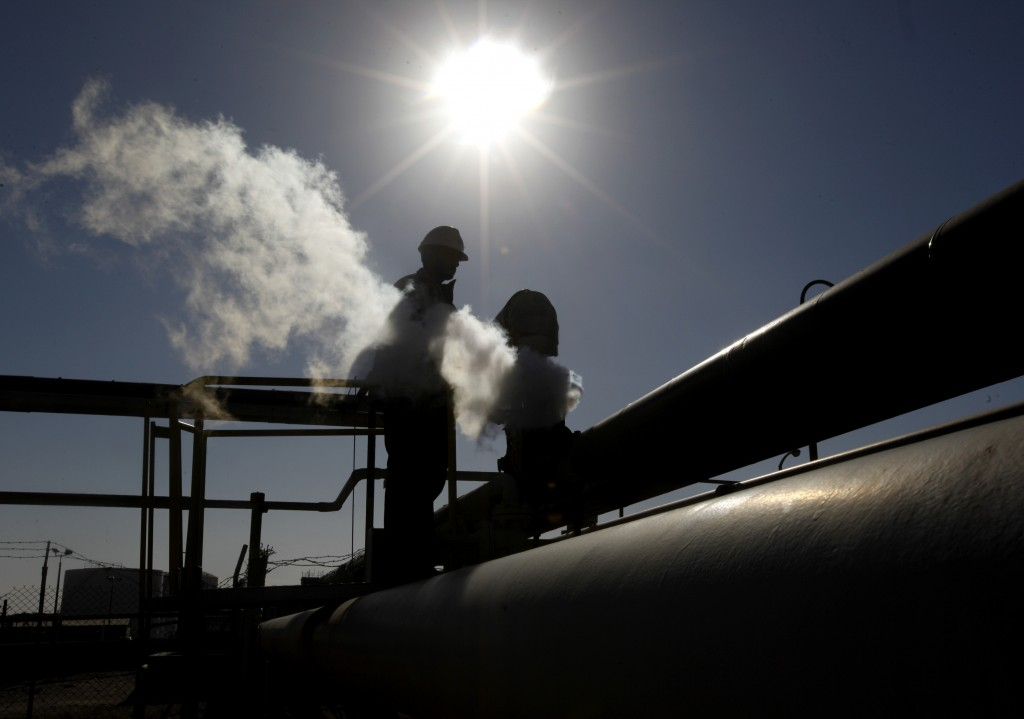 FILE - In this Feb. 26, 2011 file photo, a Libyan oil worker, works at a refinery inside the Brega oil complex, in Brega, eastern Libya.  ON Saturday,...