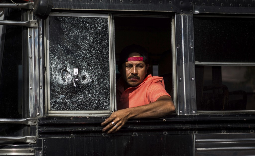 A bus driver peers from his window, which he said was shot a few weeks ago, as he drives slowly through a security checkpoint in the El Milagro area o...