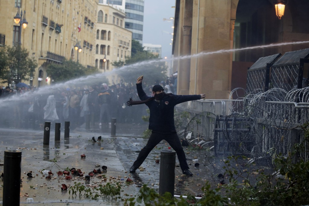 An anti-government demonstrator throws a stone toward riot police at a road leading to the parliament building in Beirut, Lebanon, Saturday, Jan. 18, ...
