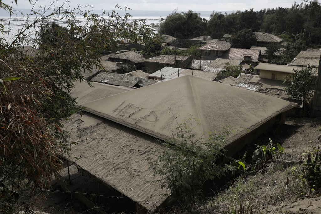 """A roof covered with volcanic ash shows a sign """"help"""" at a lakeshore village beside Taal volcano where residents have evacuated to safer ground in Agon..."""