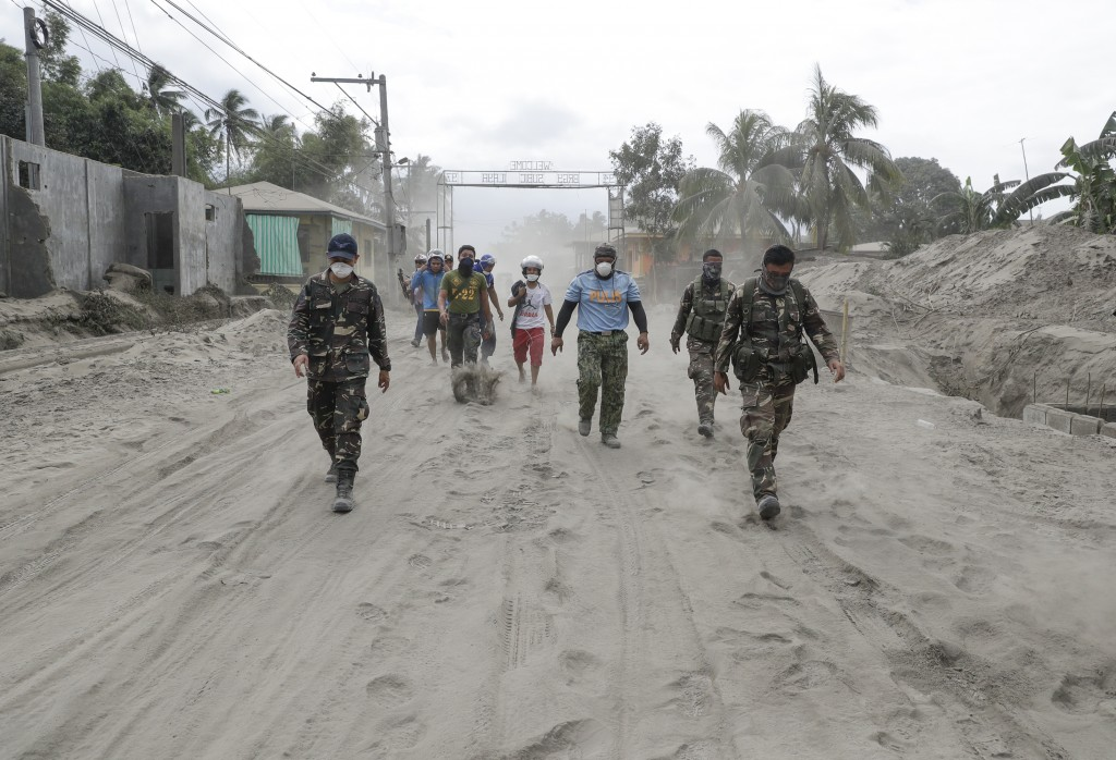 Police and military men walk along a road covered in volcanic ash at a village beside Taal volcano where residents have evacuated to safer ground in A...