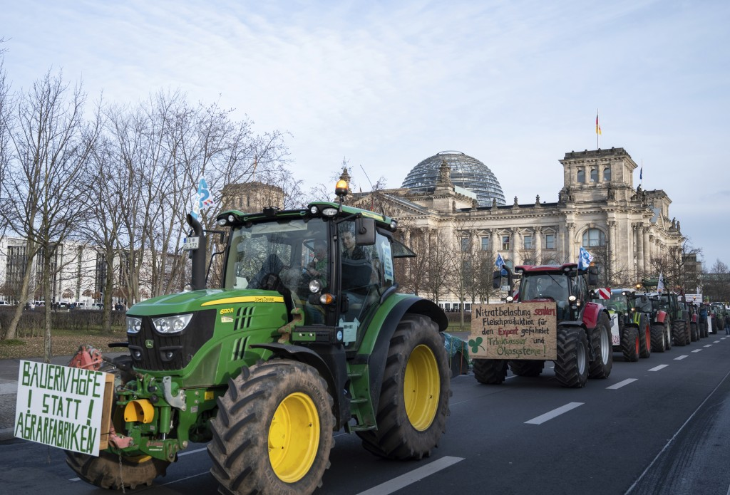 Farmers drive past the Reichstag building with their tractors in Berlin, Saturday, Jan.18, 2020. On the occasion of the Green Week agricultural and fo...