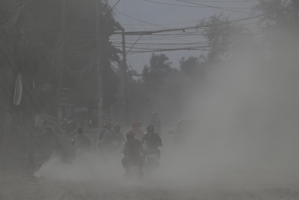 Residents on motorcycles navigate a road covered in volcanic ash at a village beside Taal volcano in Agoncillo, Batangas province, southern Philippine...