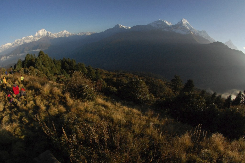 FILE - In this Oct. 24, 2014, file photo, trekkers watch the sun rise over the Annapurna Range, right, in central Nepal, as viewed from Poon Hill, abo...