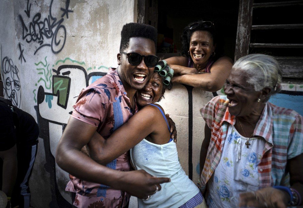 Cuban singer Cimafunk hugs a woman during a music conga through the streets of Old Havana within the activities of the 35th Havana Jazz Plaza festival...