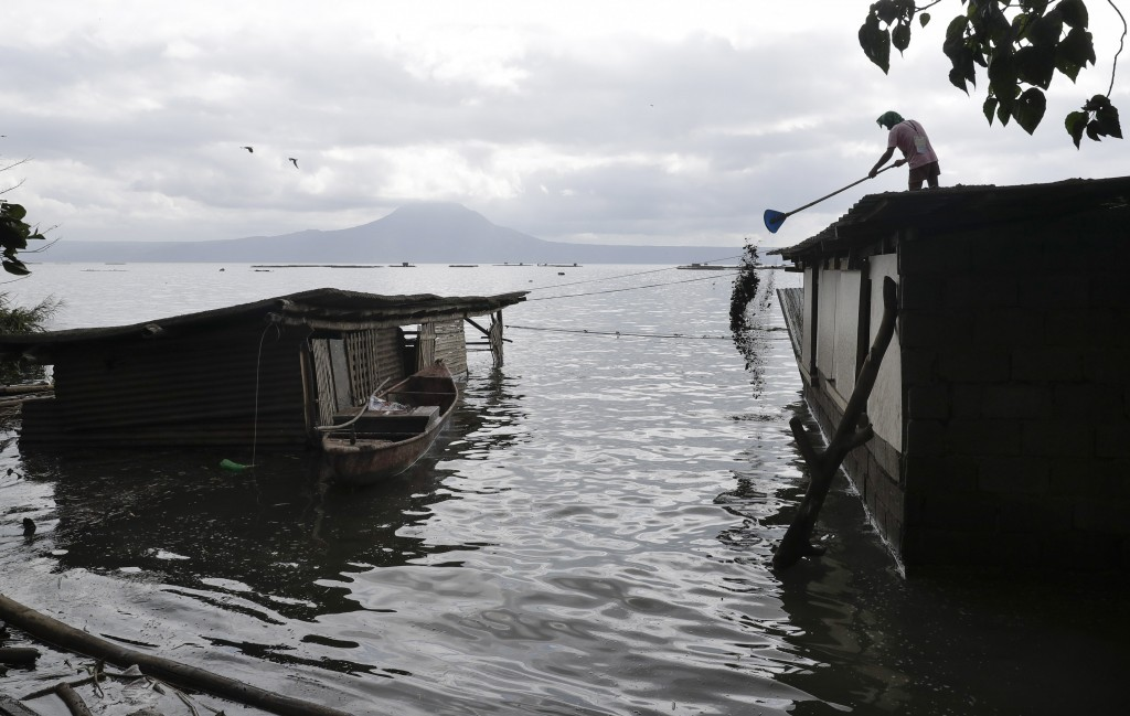 A man clears out volcanic ash from his roof at a lakeshore village where water has already reached their homes after Taal volcano'fs recent eruption i...