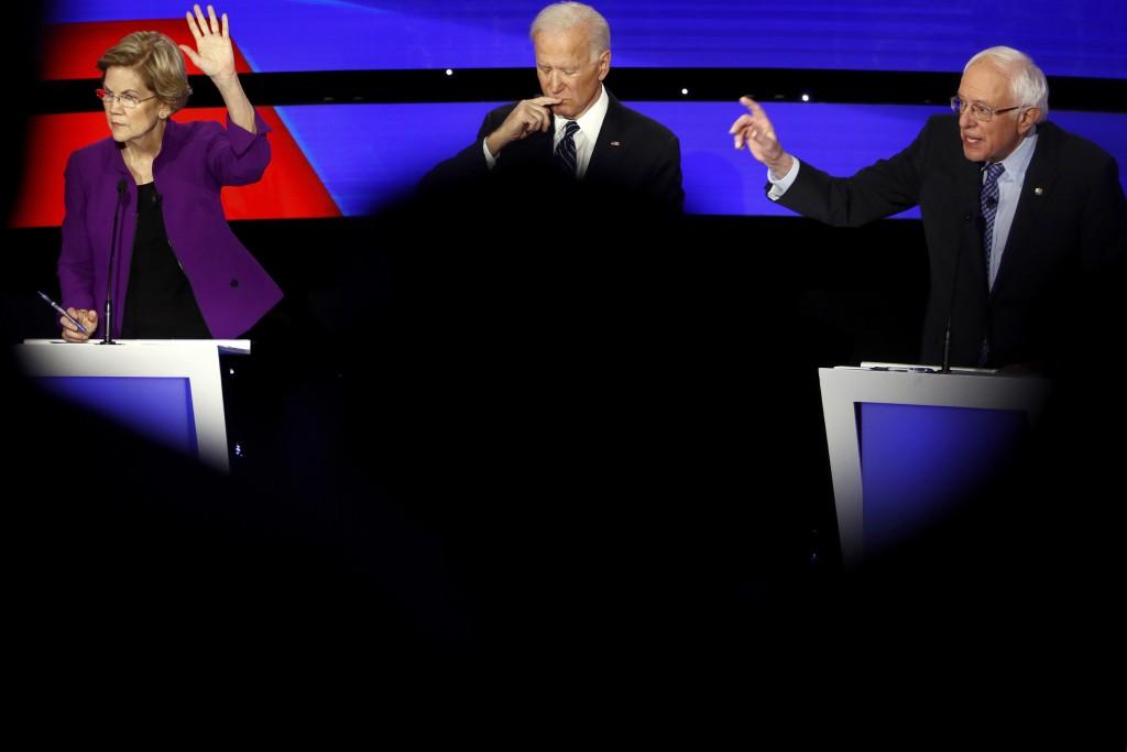 Democratic presidential candidate Sen. Elizabeth Warren, D-Mass., and Sen. Bernie Sanders, I-Vt., raise their hands to answer a question as Joe Biden ...