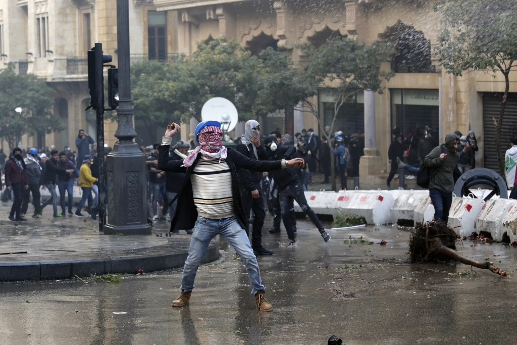 Anti-government demonstrators throw stones toward riot police at a road leading to the parliament building in Beirut, Lebanon, Saturday, Jan. 18, 2020...