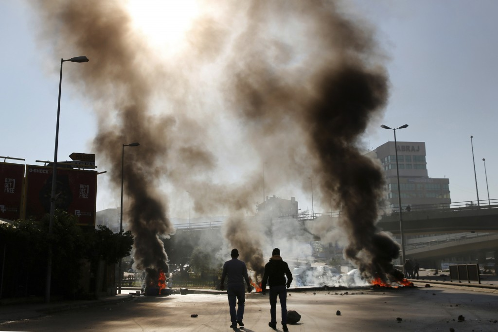 Two men walk near burning tires set on fire by anti-government protesters during ongoing protests after weeks of calm in Beirut, Lebanon, Tuesday, Jan...