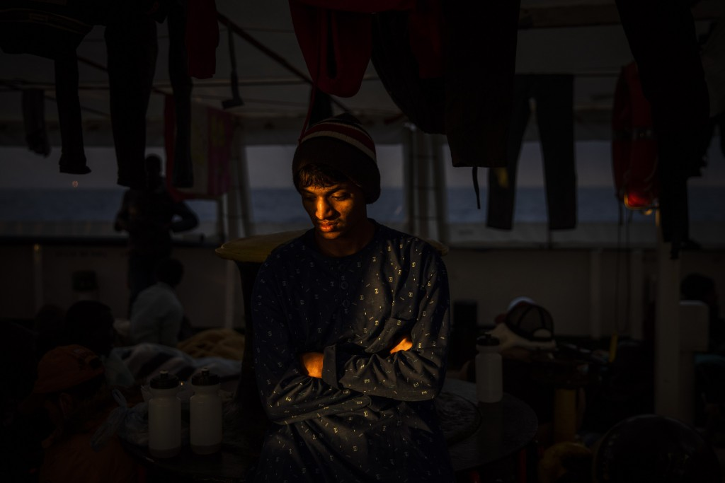 Emon, 18, from Bangladesh rests aboard the Open Arms rescue vessel as the ship sails north Sunday Jan. 12, 2020 with 118 people from different nationa...