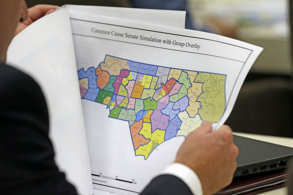 FILE - In this July 26, 2017, file photo, a lawmaker studies a district map during a joint select committee meeting on redistricting in Raleigh, N.C. ...