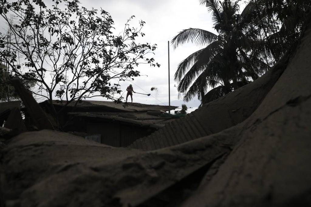 A man shovels volcanic ash from his roof at a lakeshore village beside Taal volcano where residents have evacuated to safer ground in Agoncillo, Batan...