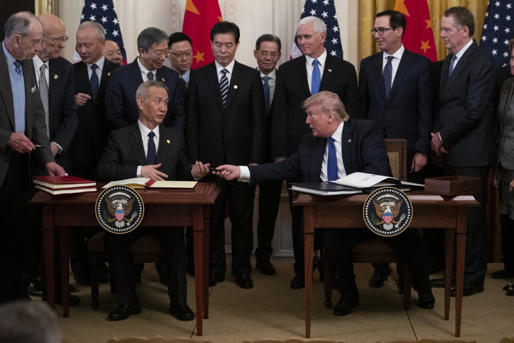"In this Jan. 15, 2020, photo, President Donald Trump hands a pen to Chinese Vice Premier Liu He after signing ""phase one"" of a US China trade agreemen..."