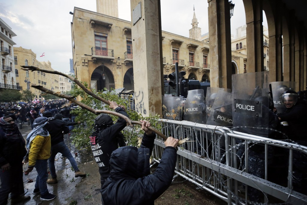 Anti-government demonstrators clash with riot police at a road leading to the parliament building in Beirut, Lebanon, Saturday, Jan. 18, 2020. Riot po...