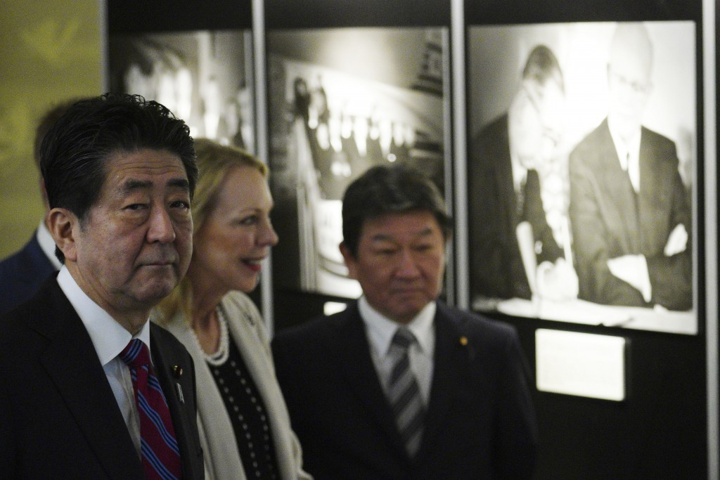 Mary Jean Eisenhower, granddaughter of former U.S. President Dwight D. Eisenhower, center, and Japan's Prime Minister Shinzo Abe, left, watch a photo ...