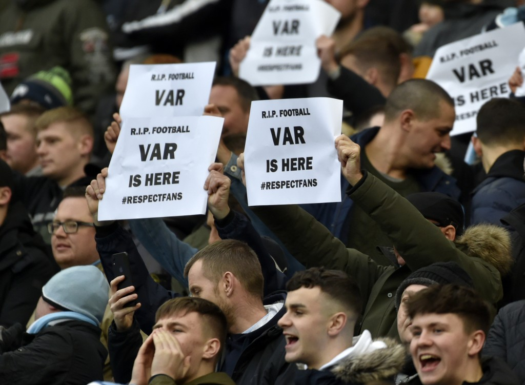 Fans hold banners against Video Assistant Referee (VAR) during the English Premier League soccer match between Manchester City and Crystal Palace at E...