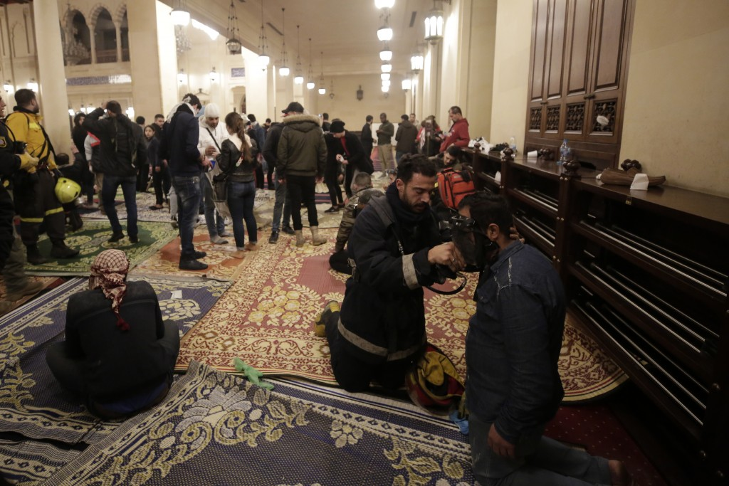 An anti-government protester receives treatment after confrontation with Lebanese riot police inside the Mohammad al-Amin Mosque during a protest in B...