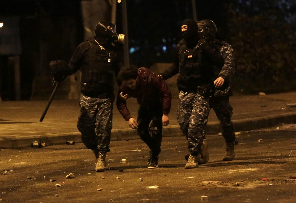 Lebanese police arrest an anti-government protester after dispersing a protest in Beirut, Lebanon, Saturday, Jan. 18, 2020. Police fired volleys of te...
