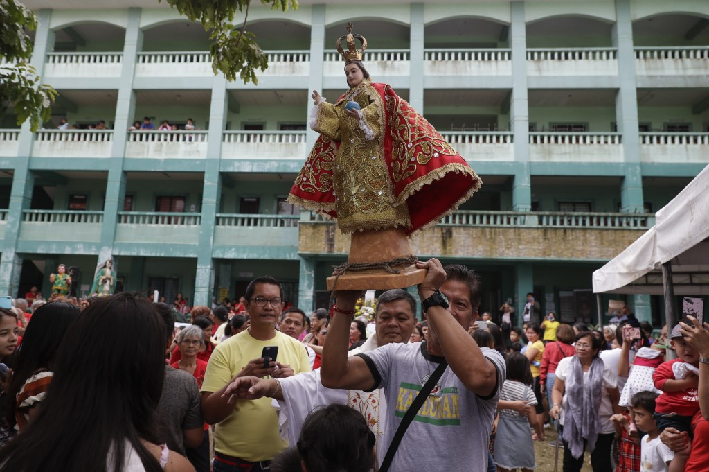 A man dances with a statue of the baby Jesus after a mass to celebrate it's feast day at an evacuation center near Taal volcano in Tagaytay, Cavite pr...