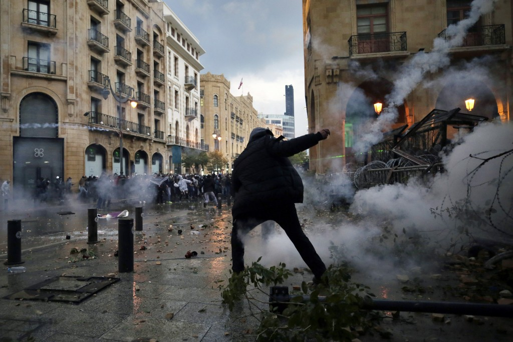 Anti-government protesters clash with the riot police, during a protest at a road leading to the parliament building in Beirut, Lebanon, Saturday, Jan...