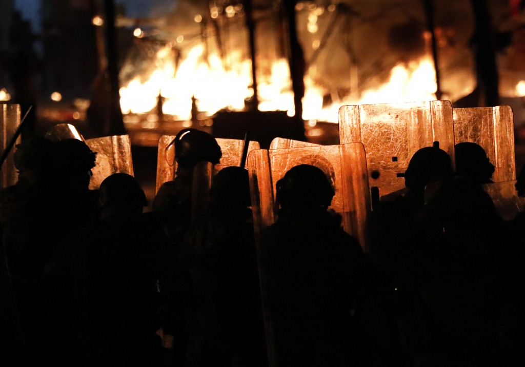 Riot policemen watch flames rise from the tents of anti-government protesters, which where set on fire by civilian men believed to be the private unit...