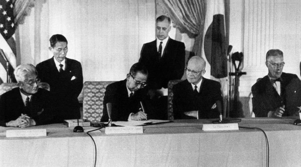 Japan's Prime Minister Nobusuke Kishi signs the U.S.-Japan mutual security treaty, on Jan. 19, 1960, in Washington. From left to right are: Foreign Mi...