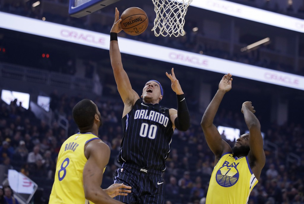 Orlando Magic's Aaron Gordon (00) lays up a shot between Golden State Warriors' Alec Burks,left, and Eric Paschall, right, during the first half of an...