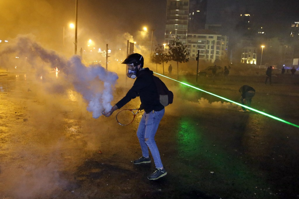 An anti-government demonstrator throws back tear gas at riot policemen with a tennis racket, in Beirut, Lebanon, Saturday, Jan. 18, 2020. Riot police ...