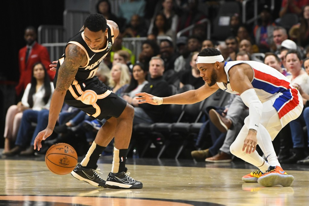 Atlanta Hawks guard Jeff Teague reaches for the ball lost by Detroit Pistons guard Bruce Brown, right, during the first half of an NBA basketball game...