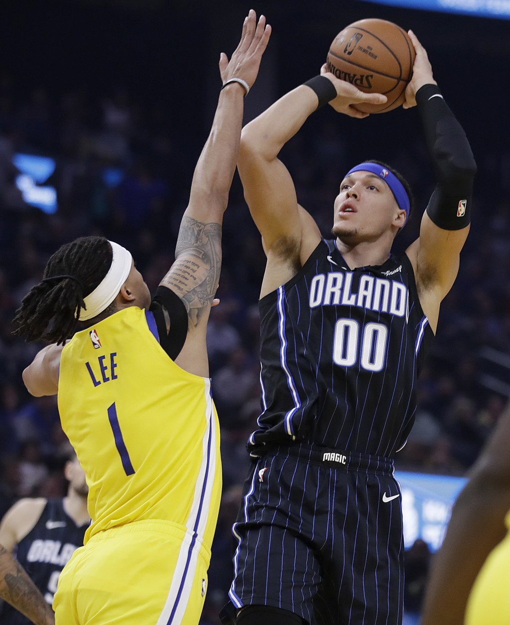 Orlando Magic's Aaron Gordon, right, shoots against Golden State Warriors' Damion Lee, left, bin the first half of an NBA basketball game Saturday, Ja...