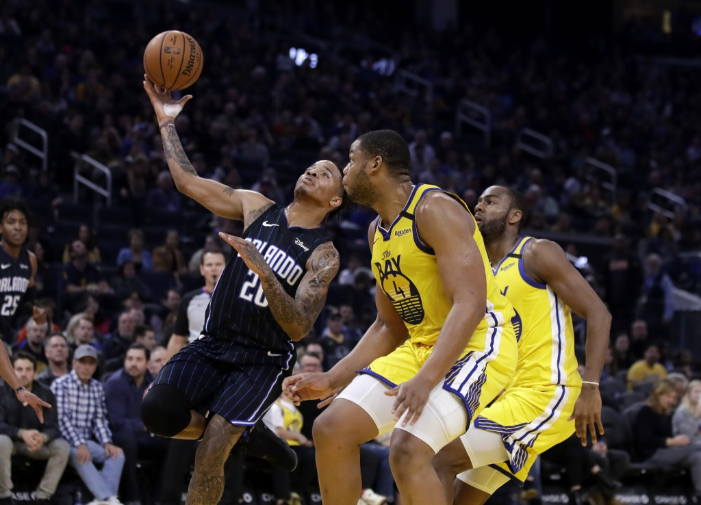 Orlando Magic's Markelle Fultz, left, shoots past Golden State Warriors' Omari Spellman, right, during the first half of an NBA basketball game Saturd...