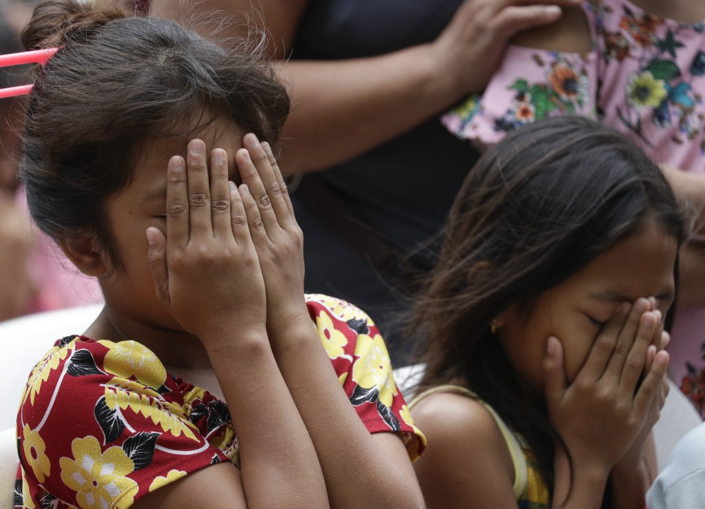 Evacuees gesture during a mass at an evacuation center near Taal volcano in Tagaytay, Cavite province, southern Philippines on Sunday Jan.19, 2020. Ta...