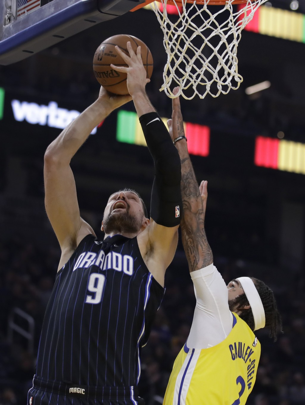 Orlando Magic's Nikola Vucevic (9) shoots against Golden State Warriors' Willie Cauley-Stein during the first half of an NBA basketball game Saturday,...