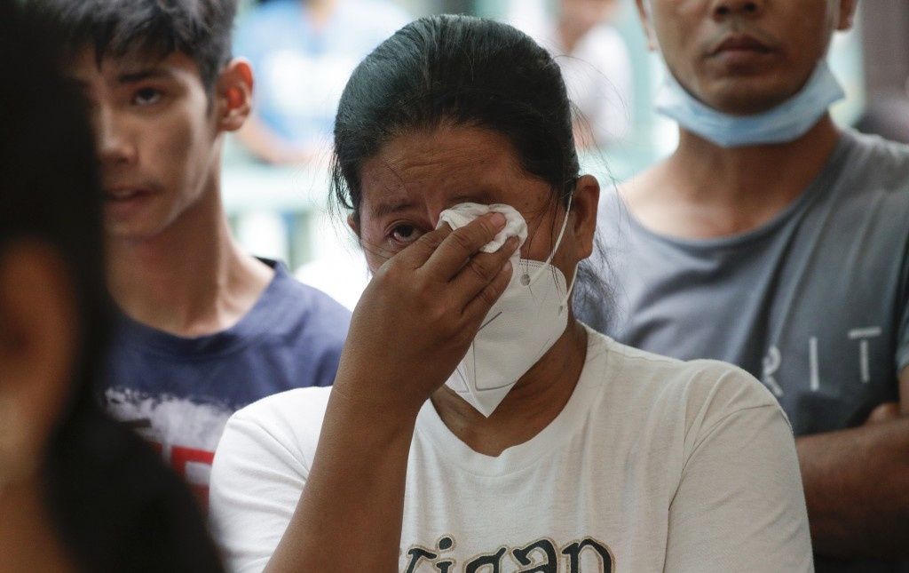 An evacuee wipes tears during a mass at an evacuation center near Taal volcano in Tagaytay, Cavite province, southern Philippines on Sunday Jan.19, 20...