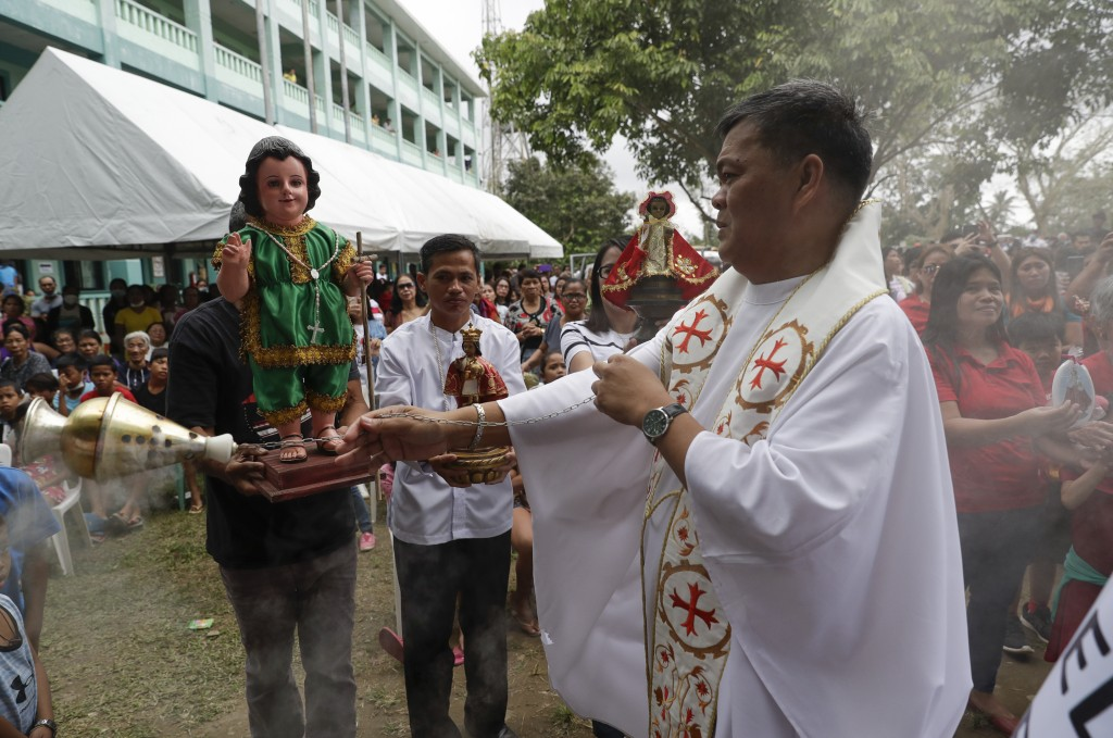 Catholic priest Armando Timojo, right blesses images of the baby Jesus after a mass to celebrate it's feast day at an evacuation center near Taal volc...