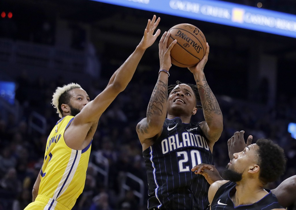 Orlando Magic's Markelle Fultz,center, shoots against Golden State Warriors' Ky Bowman, left, during the first half of an NBA basketball game Saturday...