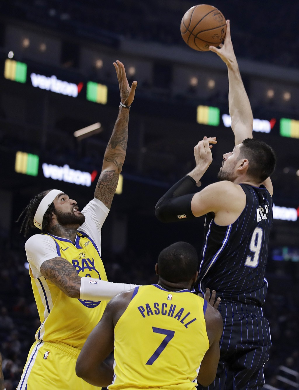 Orlando Magic Nikola Vucevic, right, shoots over Golden State Warriors' Willie Cauley-Stein, left, and Eric Paschall, right, during the first half of ...