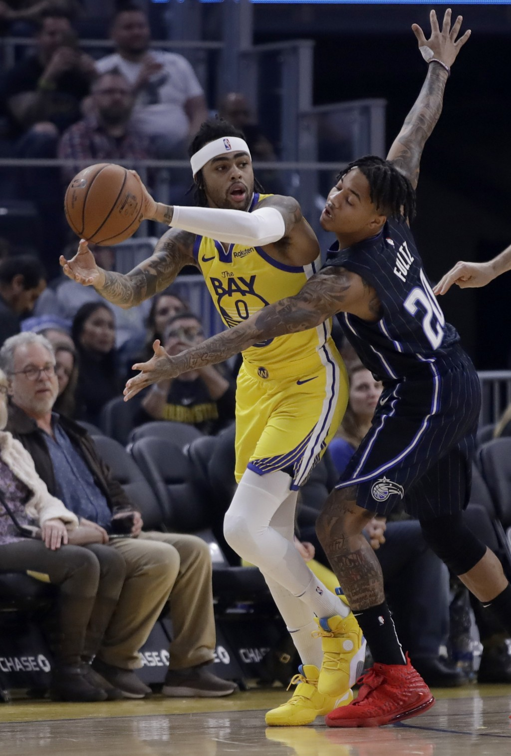 Golden State Warriors' D'Angelo Russell, left, looks to pass away from Orlando Magic's Markelle Fultz (20) during the first half of an NBA basketball ...