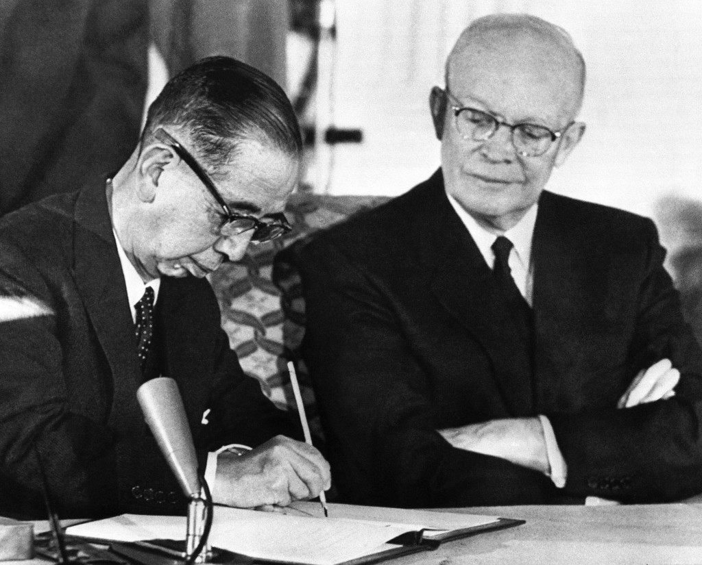 Japanese Prime Minister Nobusuke Kishi signs a treaty of mutual security with the United States on Jan. 19, 1960 in Washington. President Dwight D. Ei...
