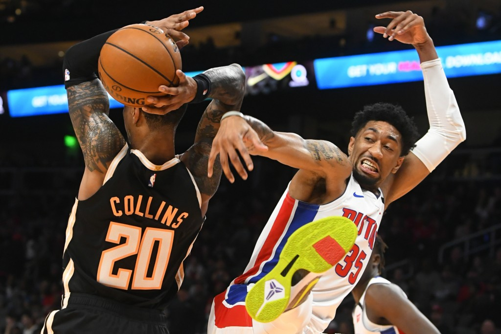 Detroit Pistons forward Christian Wood, right, comes down after blocking a shot by Atlanta Hawks forward John Collins (20) during the first half of an...
