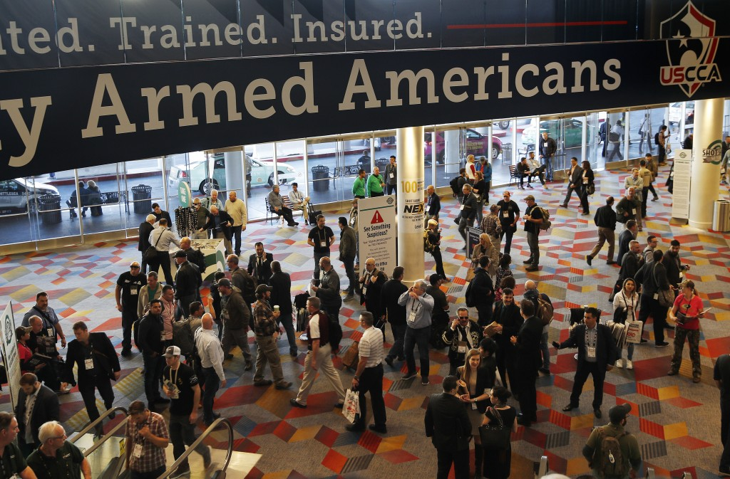 FILE - In this Wednesday, Jan. 24, 2018, file photo, people walk through the hall outside of the SHOT Show gun show in Las Vegas. The gun industry is ...