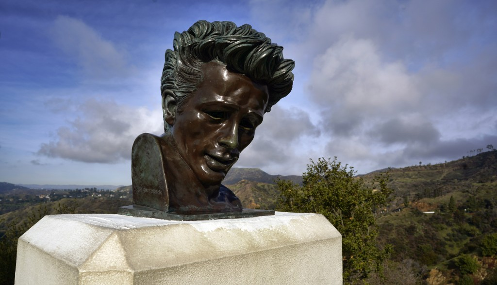 In this Friday, Jan. 17, 2020, photo, the Hollywood hills are seen behind a bust of actor James Dean at the Griffith Observatory in Los Angeles. Travi...